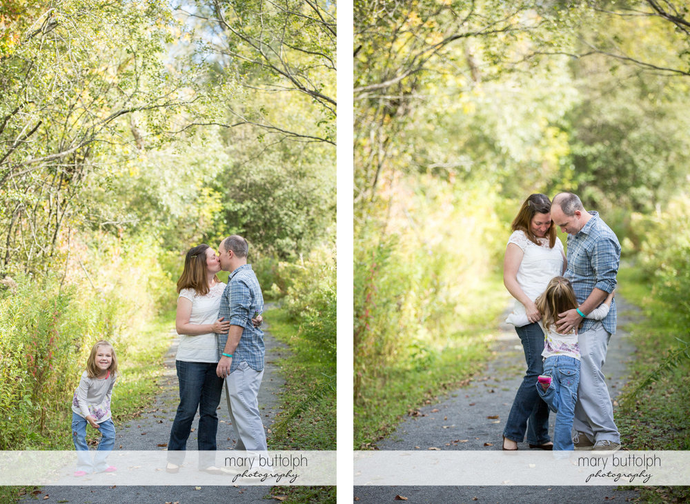 Couple kiss before they are interrupted by their daughter at Skaneateles Engagement