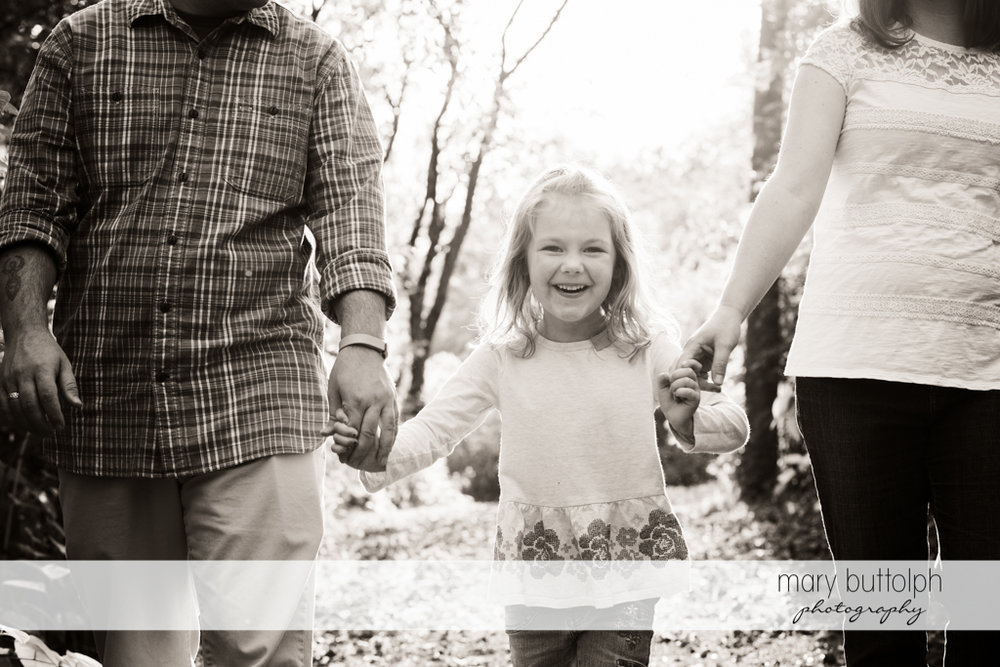 Couple stroll with their daughter in the park at Skaneateles Engagement