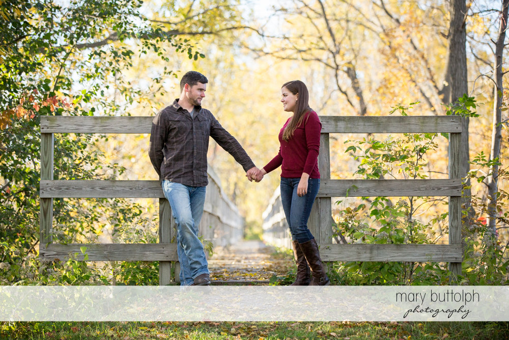 Couple hold hands in front of a wooden bridge at Geneva Engagement