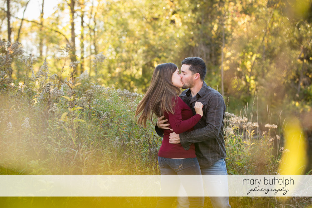 Couple kiss passionately at the farm at Geneva Engagement