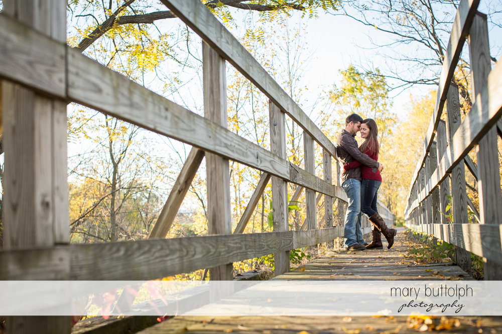 Couple stop in the middle of a wooden bridge at Geneva Engagement