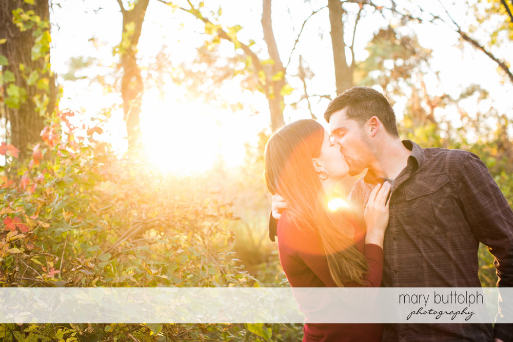 Couple kiss as the sun shines in the background at Geneva Engagement