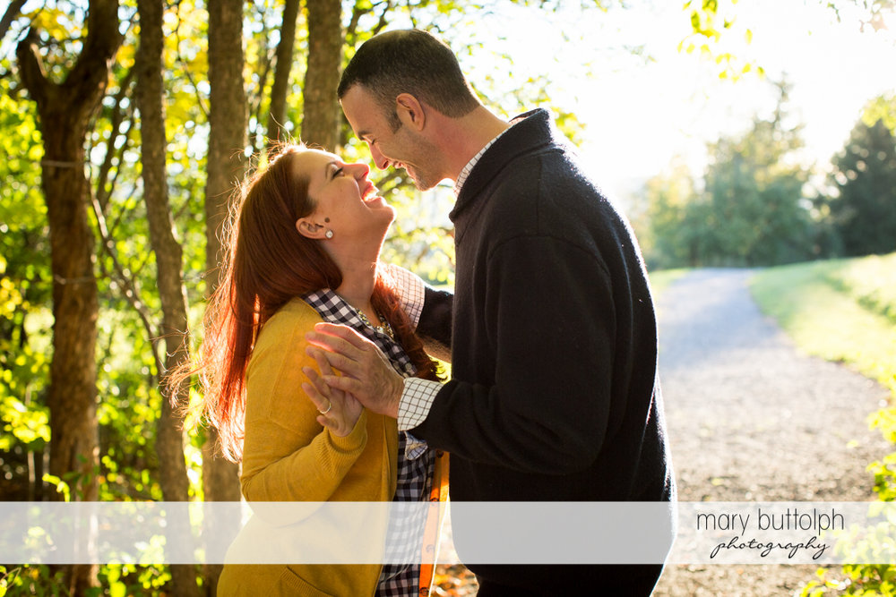Couple laugh in the park at Cazenovia Engagement
