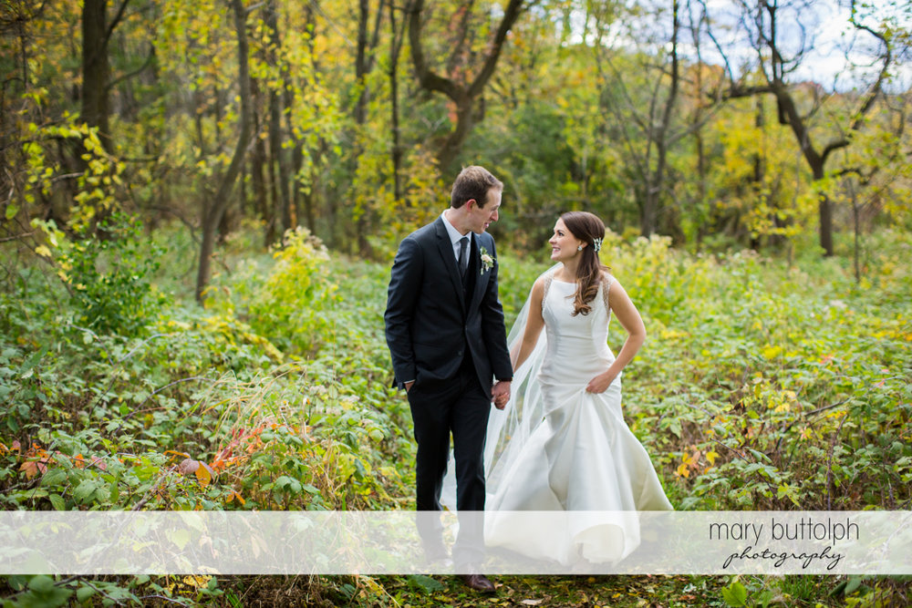 Couple stroll in the woods at Frog Pond Bed & Breakfast Wedding
