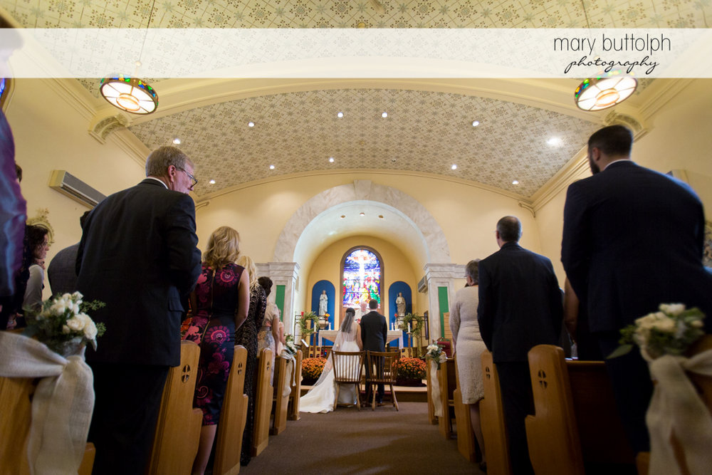 Couple face the altar as guests look on at the Frog Pond Bed & Breakfast Wedding