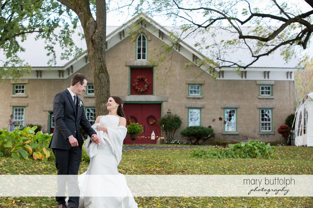 Couple walk away from the carriage barn at the Frog Pond Bed & Breakfast Wedding