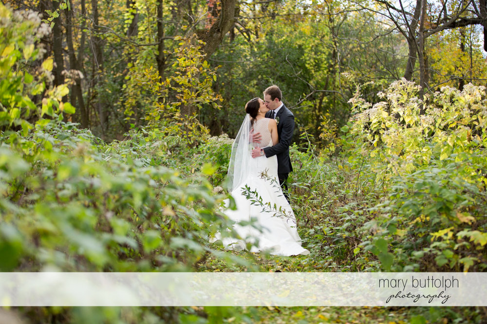 Couple kiss in the woods at the Frog Pond Bed & Breakfast Wedding