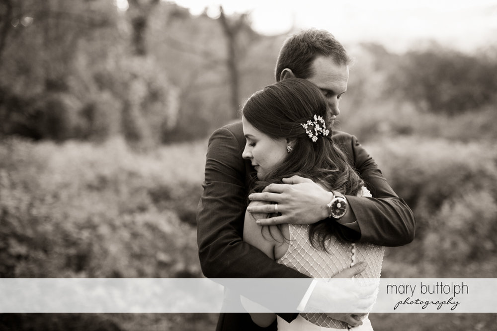 Couple show their love in this stunning black and white shot in the woods at the Frog Pond Bed & Breakfast Wedding