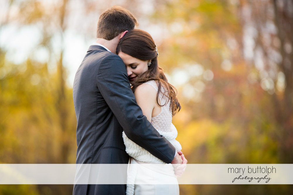Couple share a tender moment in the woods at the Frog Pond Bed & Breakfast Wedding