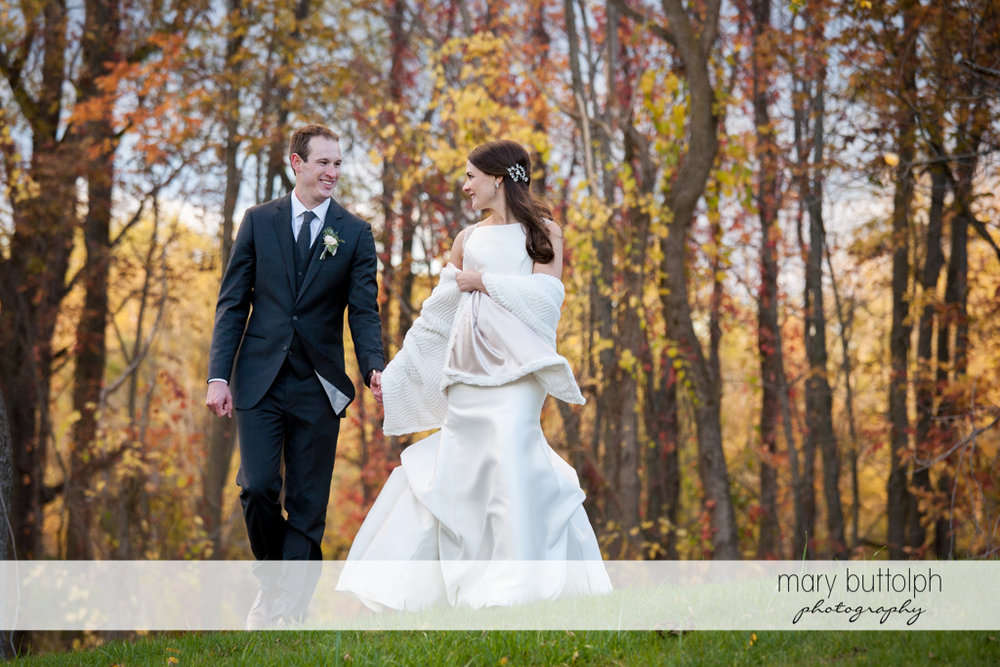 Couple hold hands while strolling in the woods at the Frog Pond Bed & Breakfast Wedding