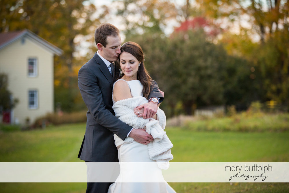 Couple show their romantic side in front of the carriage barn at the Frog Pond Bed & Breakfast Wedding
