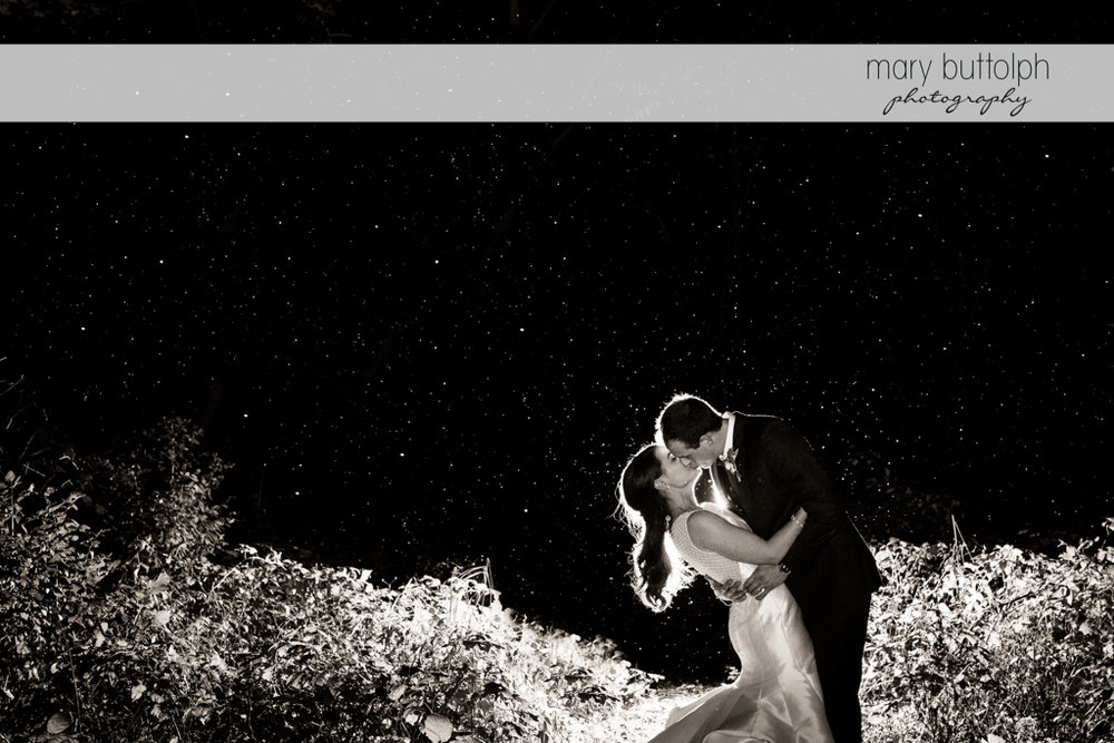 Couple kiss in the garden on a starry night at the Frog Pond Bed & Breakfast Wedding