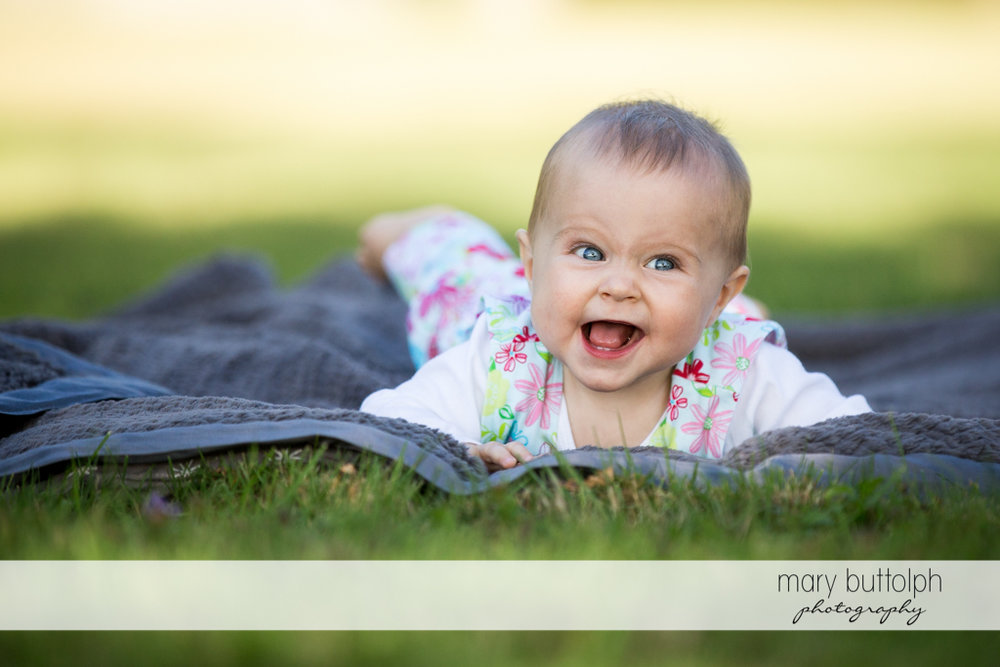 Baby girl flashes a big smile in the garden at Skaneateles Lake