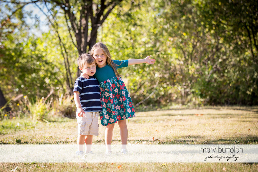 Girl poses with her brother in front of trees in the garden at Skaneateles Lake