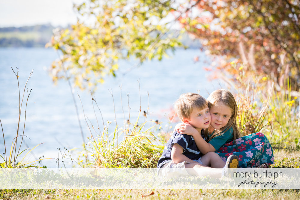 Siblings sit on the grass near the lake at Skaneateles Lake2