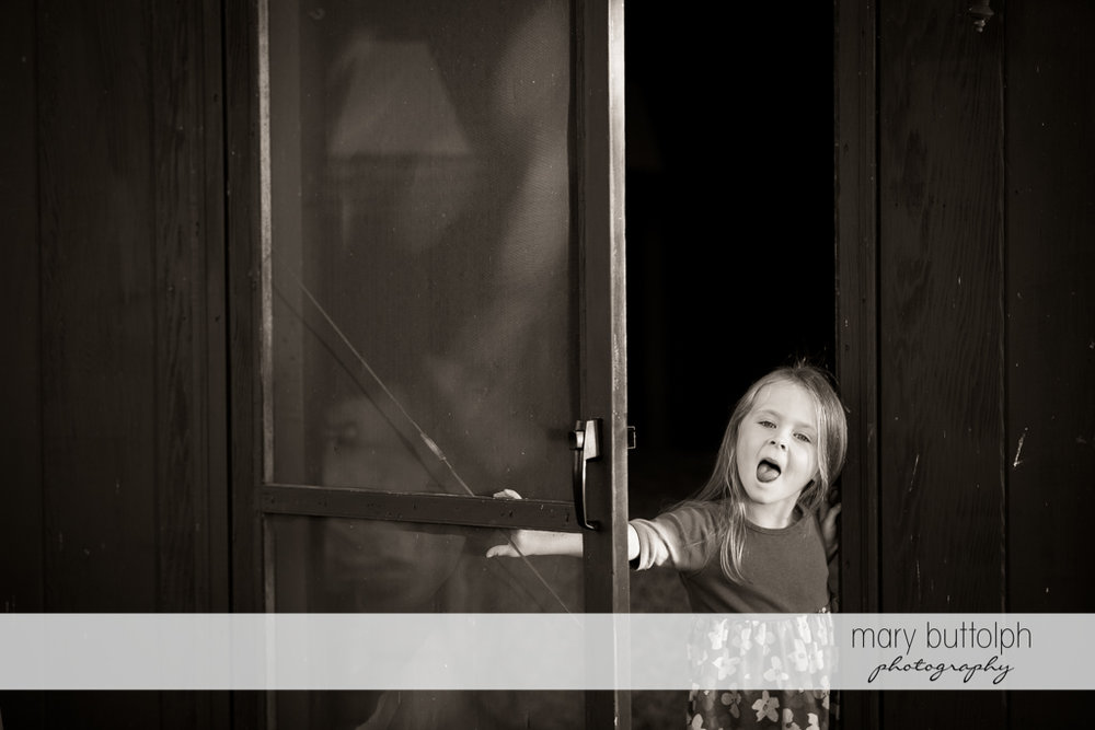 Girl greets guests at the front door of her home with a funny face at Skaneateles Lake