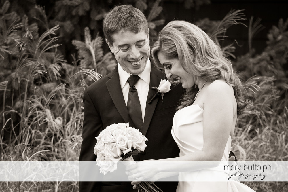 Couple share a happy moment in the garden at the Lodge at Welch Allyn Wedding