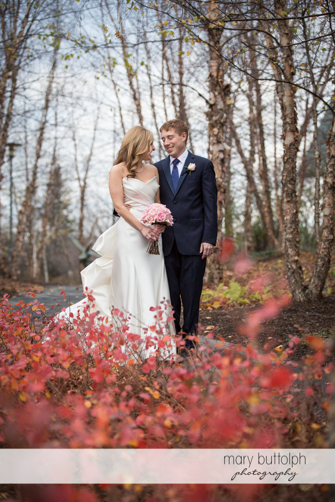 Couple pass by pink plants as they stroll in the woods at the Lodge at Welch Allyn Wedding