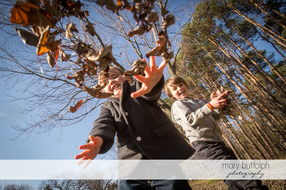 Boys throw leaves in the backyard at Skaneateles