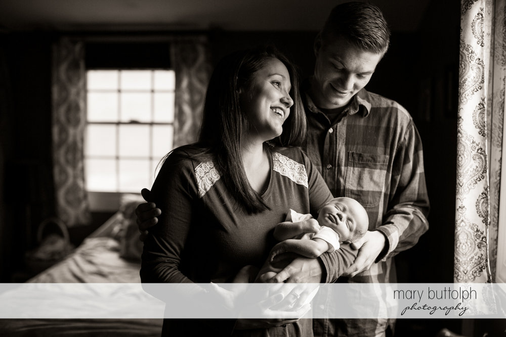 Couple admire their new baby in a dramatic black and white shot at Skaneateles Newborn