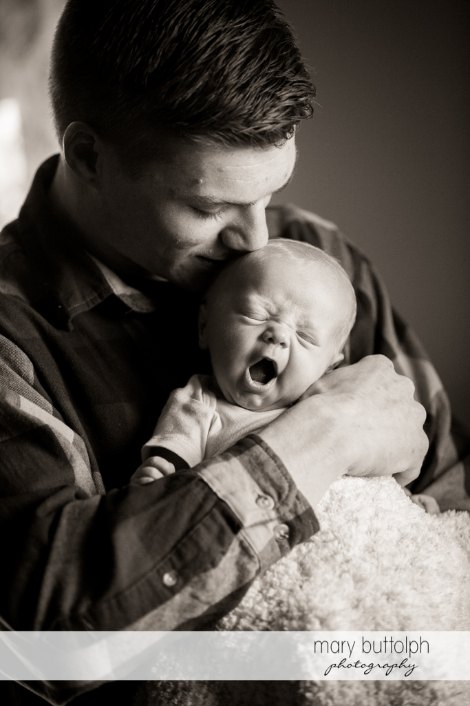 Man kisses his yawning baby at Skaneateles Newborn
