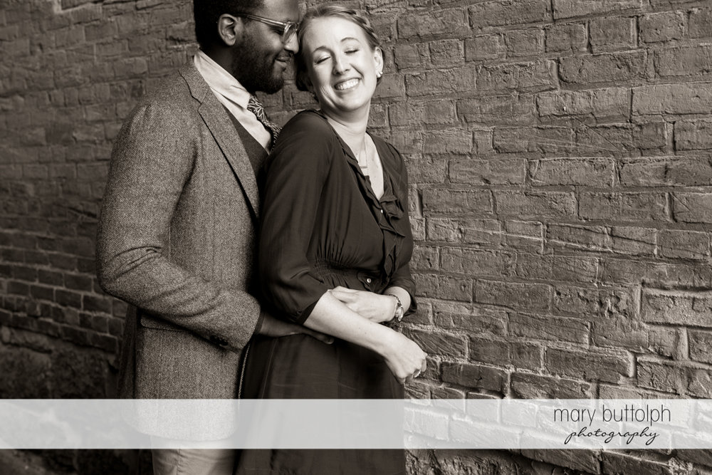 Couple having a great time in front of a brick wall at Skaneateles Engagement