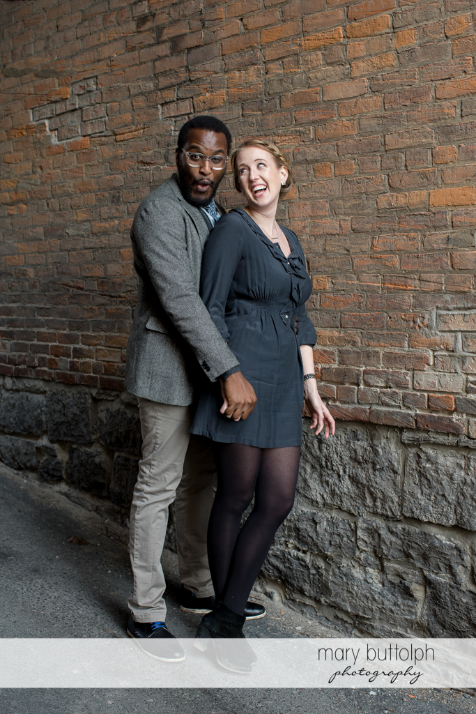 Couple clown around in front of a brick wall at Skaneateles Engagement