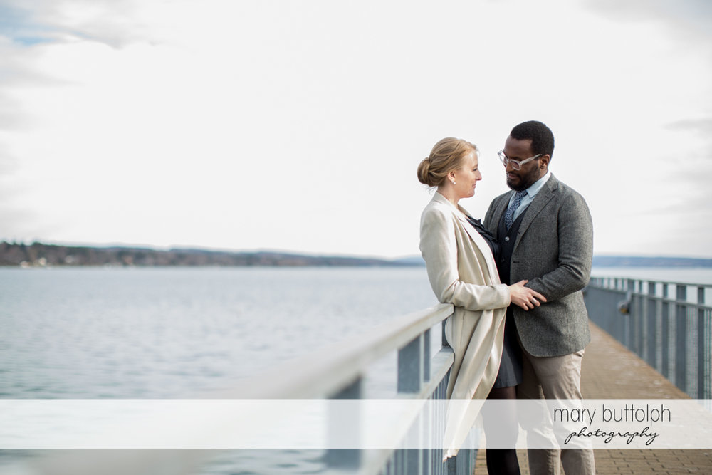 Couple hold hands by the lake at Skaneateles Engagement