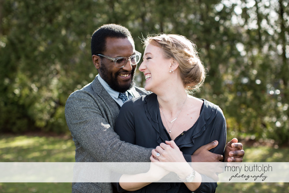 Couple share a light moment in the park at Skaneateles Engagement
