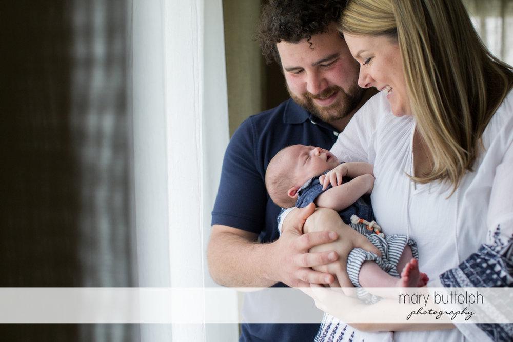 Couple admire their sleeping baby at Syracuse Newborn