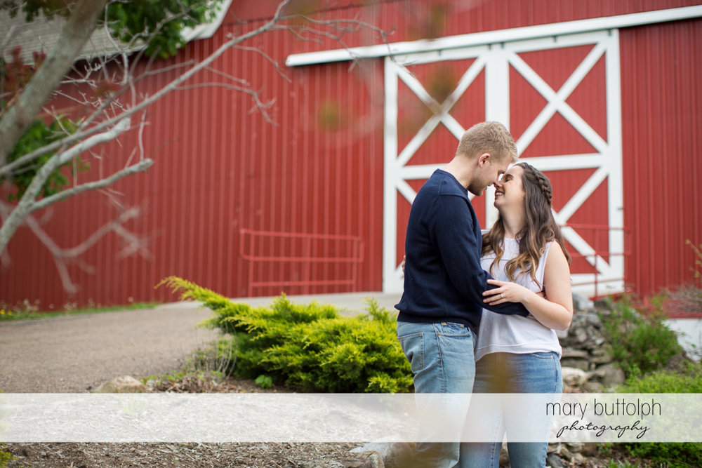 Couple pose in front of the farmhouse at Hobbit Hollow Engagement