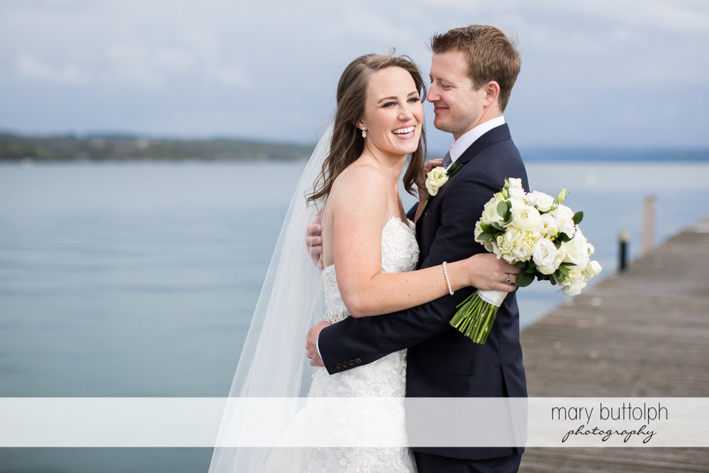 Couple embrace near the lake at Skaneateles Country Club Wedding