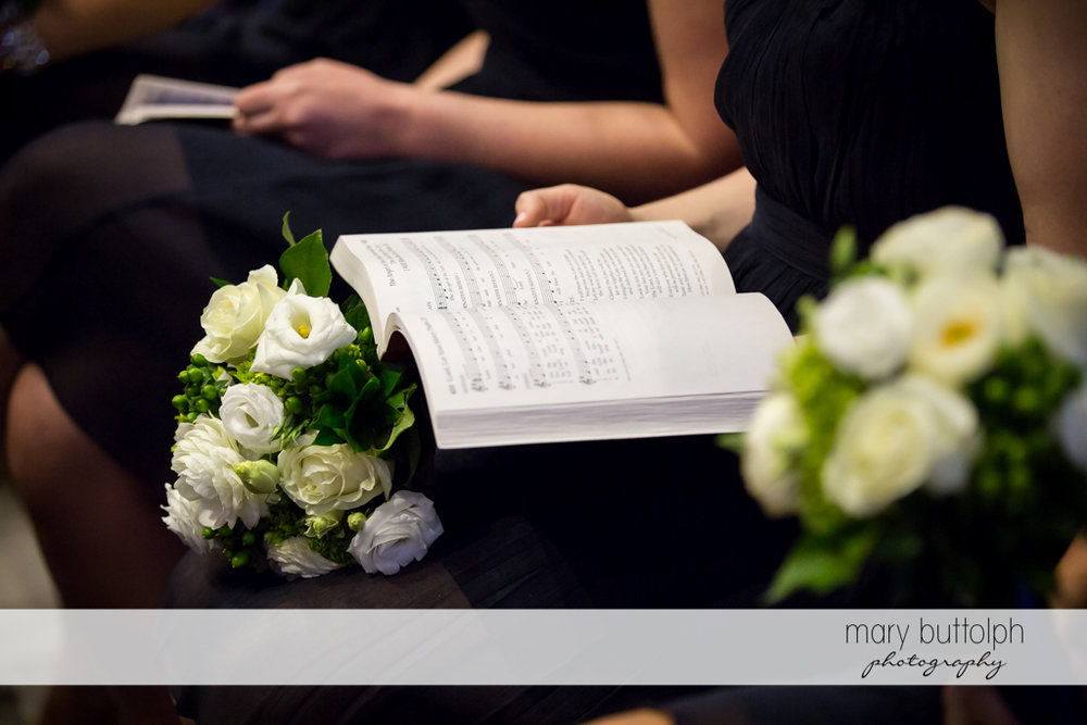 Guest with flowers reads the hymnal at Skaneateles Country Club Wedding