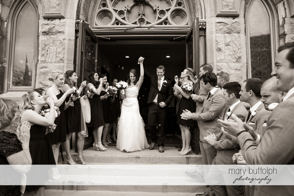 Couple are greeted with bubbles by other members of the wedding party outside the church at Skaneateles Country Club Wedding