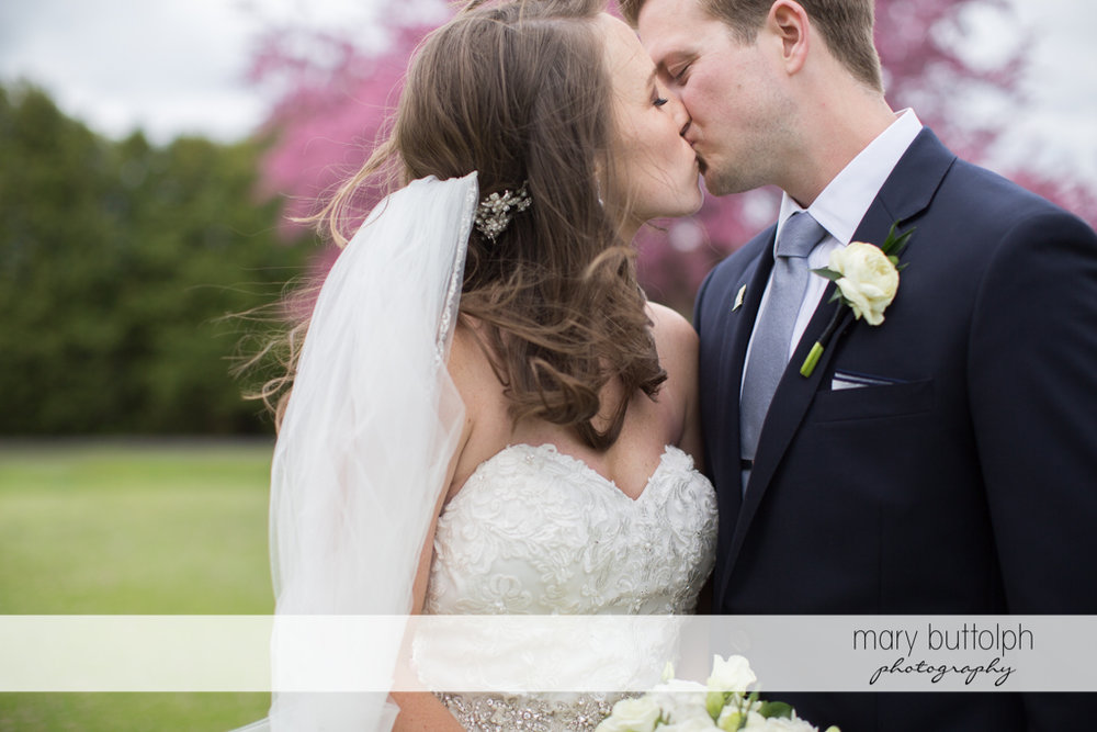 Couple kiss in the garden at Skaneateles Country Club Wedding