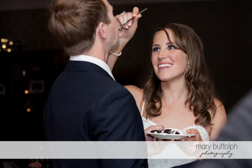 Bride feeds her husband with a slice of the wedding cake at Skaneateles Country Club Wedding
