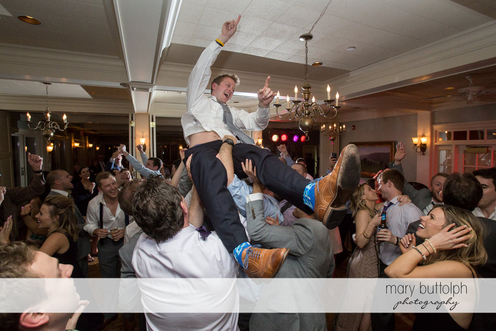 Groom is lifted up in the air by guests at Skaneateles Country Club Wedding