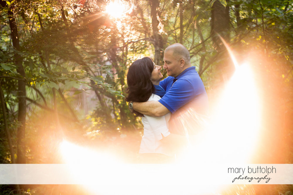 Couple embrace as sunlight surrounds them in the park at Skaneateles Engagement