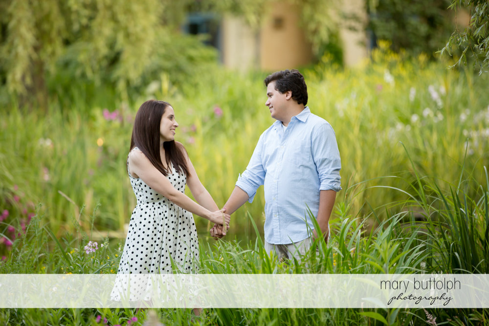 Couple hold hands in garden at Skaneateles Engagement