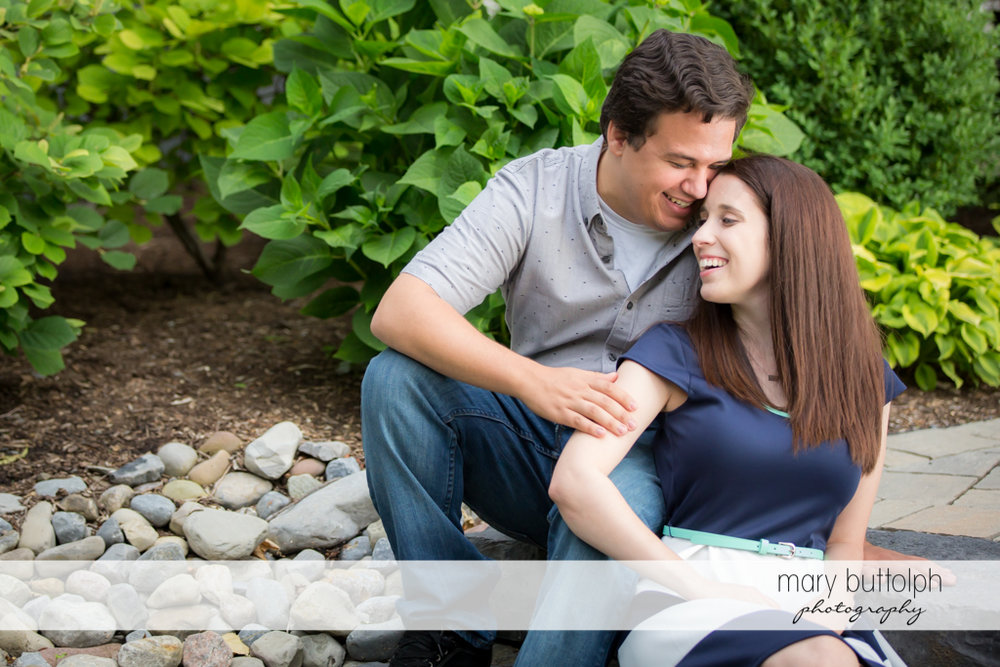 Couple sitting in front of garden at Skaneateles Engagement