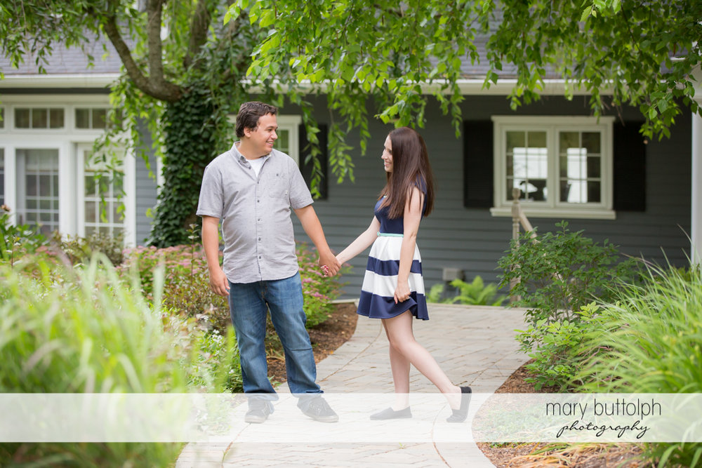 Couple hold hands in front of a house at Skaneateles Engagement