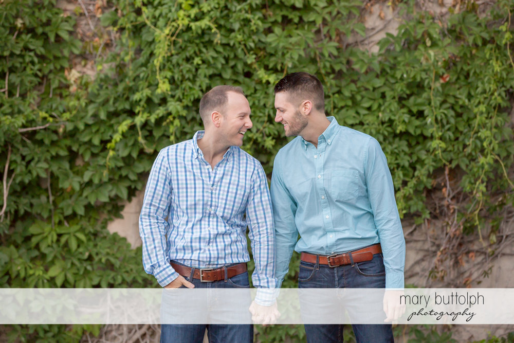 Same sex couple pose before a wall covered with plants at Skaneateles Engagement