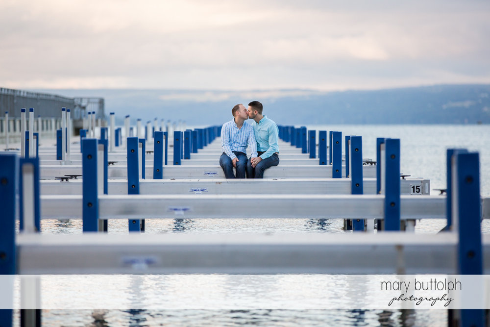 Same sex couple kiss at the docks by the lake at Skaneateles Engagement