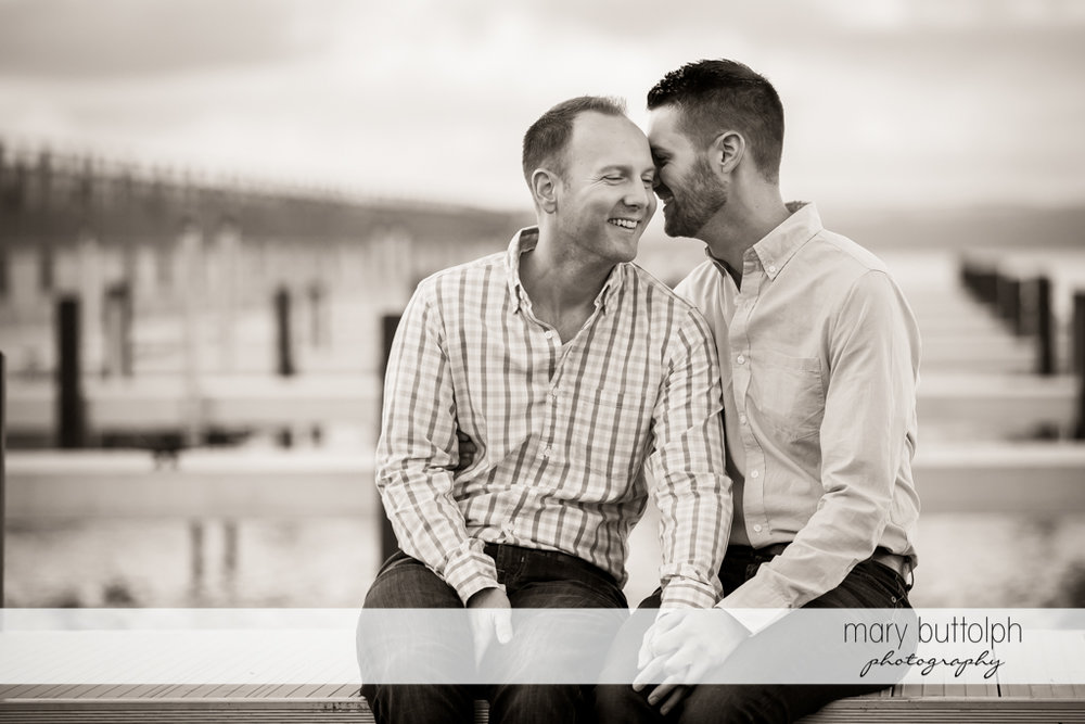 Same sex couple show their affection by the lake at Skaneateles Engagement