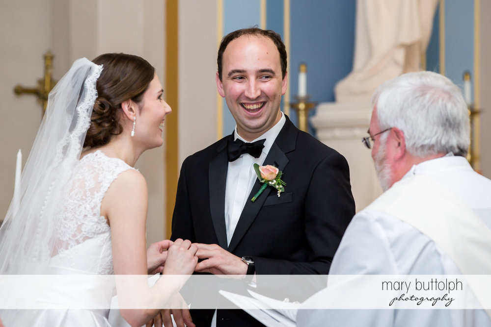 Couple hold hands in front of the priest at the Inns of Aurora Wedding