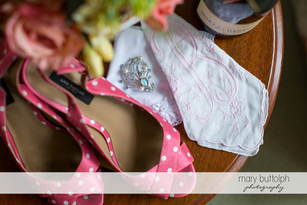 Close up shot of bride's shoes and brooch at the Inns of Aurora Wedding