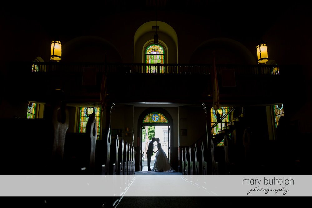 Long shot of couple kissing by the church doorway at the Inns of Aurora Wedding