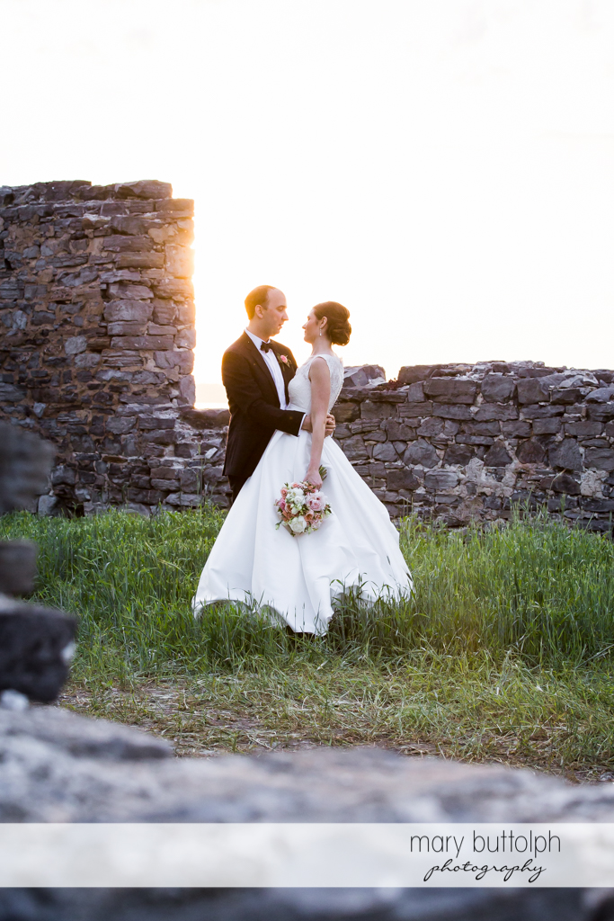 Couple stand in front of a stone wall at the Inns of Aurora Wedding