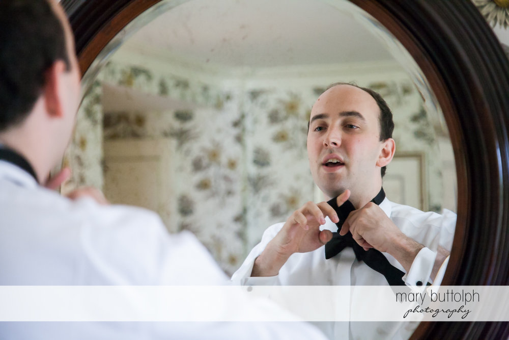 Groom fixes his tie in front of the mirror at the Inns of Aurora Wedding