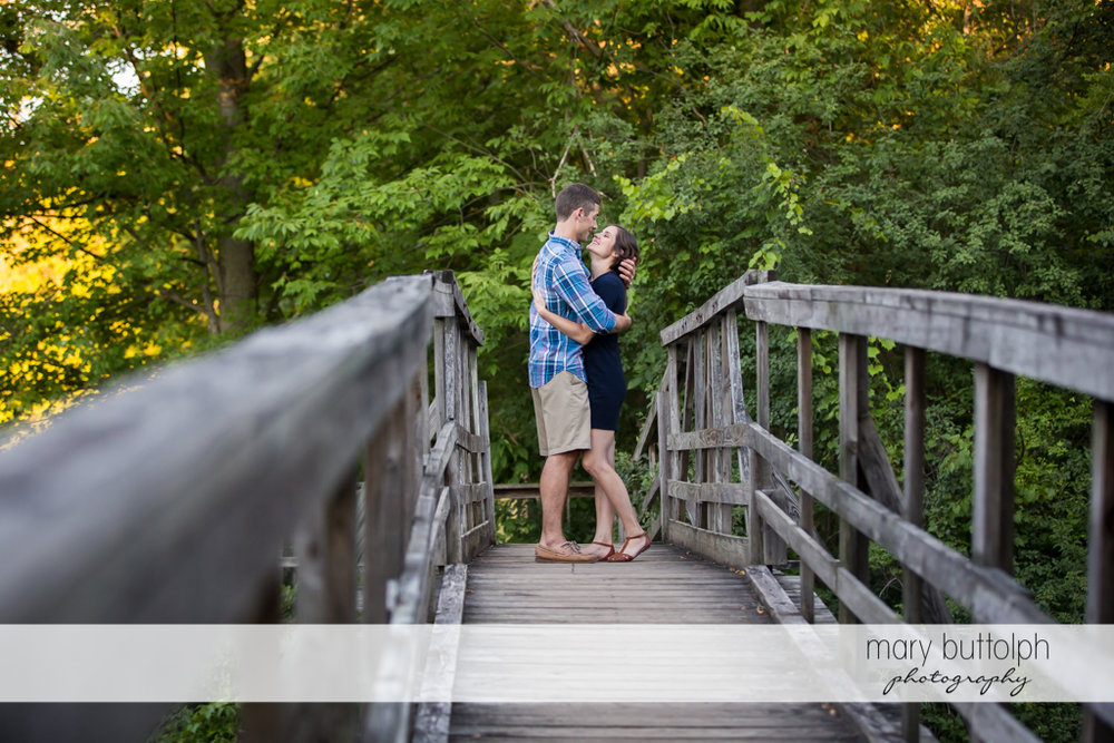 Couple embrace in the middle of an old wooden bridge at Finger Lakes Engagement